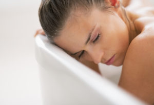 Portrait of stressed young woman in bathtub