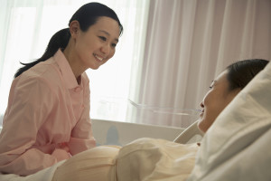 Smiling nurse talking to pregnant woman lying on bed in the hosp