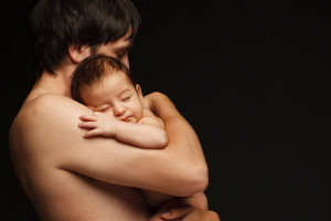 Father holding newborn baby over black background
